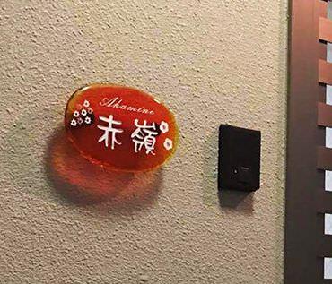 表札の設置例、壁にオレンジ色の琉球ガラスの表札が設置されています。