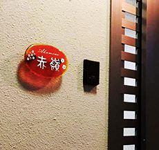 表札の設置例、壁にオレンジ色の琉球ガラスの表札が飾られている写真